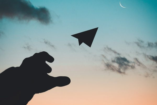 paper aeroplane being thrown into the sky